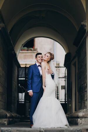 Stylish bride and groom having fun in sunny european city street. Gorgeous wedding couple of newlyweds embracing in old buildings. Romantic moment 스톡 콘텐츠
