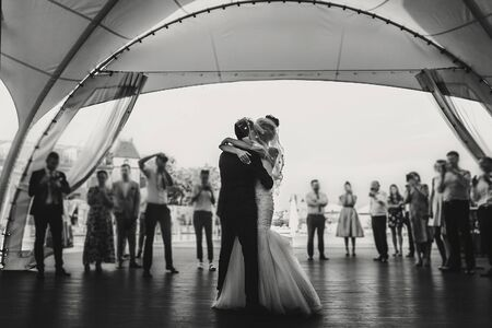 Stylish happy bride and groom gently dancing at wedding reception. Gorgeous wedding couple of newlyweds embracing while having first dance on background of guests 스톡 콘텐츠