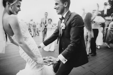 Stylish happy bride and groom having fun and dancing at wedding reception. Gorgeous wedding couple of newlyweds having first dance on background of guests Foto de archivo - 128326696