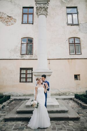 Stylish bride and groom kissing sensually in sunny european city street. Gorgeous wedding couple of newlyweds embracing at old buildings. Romantic moment Stockfoto