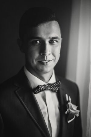 Stylish happy groom in blue suit, with bow tie and boutonniere posing and smiling near window in hotel room. Morning preparation before wedding ceremony