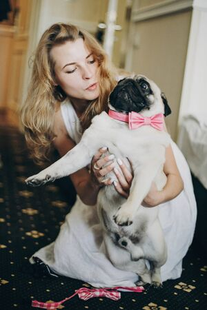 Cute bride hugging funny pug dog with pink bow tie in morning  before wedding ceremony in hotel room.Girl with her dog. Pets at wedding day.