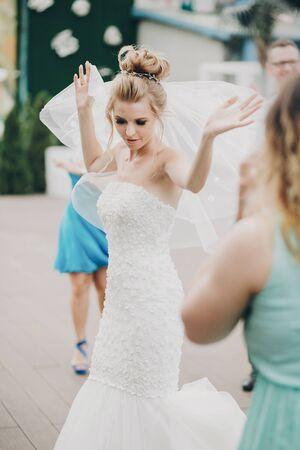 Glückliche Braut, die beim Hochzeitsempfang tanzt. Wunderschöne Hochzeitspaarbraut im weißen Kleid, die Spaß beim Tanzen mit Freunden im Restaurant hat