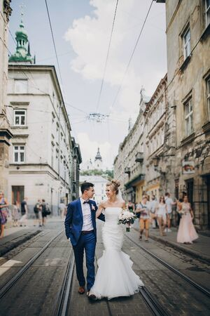 Stylish happy bride and groom walking and smiling in sunny city street. Gorgeous wedding couple of newlyweds embracing outdoors. Romantic moment Фото со стока - 128326736
