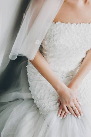 Stylish bride holding hands with pink and white nails manicure on modern dress, getting ready in hotel room. Morning preparation before wedding ceremony. 스톡 콘텐츠