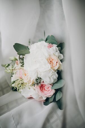 Stylish Modern wedding bouquet on white tulle in soft light in hotel room. Morning preparation before wedding ceremony. Floral arrangement for luxury event 스톡 콘텐츠