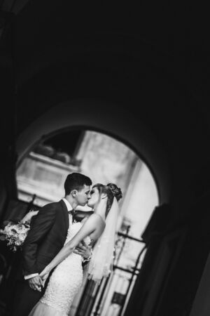 Stylish groom kissing sensually his happy bride in sunny european city street. Gorgeous wedding couple of newlyweds embracing at old building. Romantic moment Stockfoto