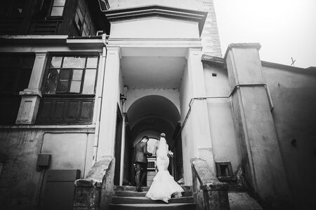 Stylish bride and groom walking in sunny european city street, back view. Gorgeous wedding couple of newlyweds embracing in old buildings. Romantic moment Stockfoto
