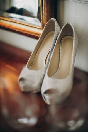 Stylish white shoes for bride on wooden table in soft morning light in hotel room. Morning preparation before wedding ceremony. Footwear for luxury event 스톡 콘텐츠