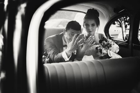 Stylish happy bride and groom showing hands with wedding rings, sitting inside of old retro car. Gorgeous wedding couple of newlyweds after wedding ceremony in car.
