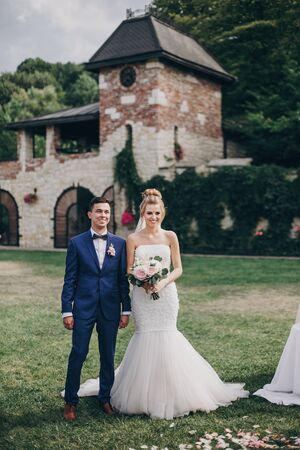 Beautiful stylish bride and groom standing in wedding aisle with rose petals on grass during matrimony, and smiling. Beautiful wedding ceremony in summer park or garden 스톡 콘텐츠