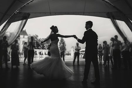 Silhouettes of happy bride and groom gently dancing at wedding reception. Gorgeous wedding couple of newlyweds embracing while having first dance on background of guests