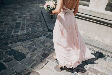 Stylish bridesmaid in pink dress walking in european city street and holding wedding bouquet, cropped view. Wedding celebration outdoors