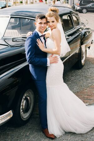 Stylish happy bride and groom posing at old retro car. Gorgeous wedding couple of newlyweds smiling and hugging after wedding ceremony. Romantic moment 스톡 콘텐츠 - 128326775
