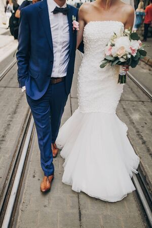 Stylish bride with bouquet and groom walking in sunny european city street, cropped view. Gorgeous wedding couple of newlyweds embracing outdoors. Romantic moment