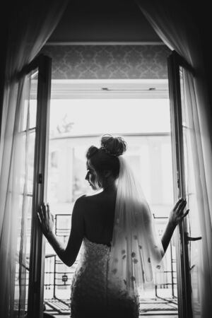 Silhouette of stylish bride opening window balcony in soft light in hotel room. Back of gorgeous sensual bride in white gown. Morning preparation before wedding ceremony