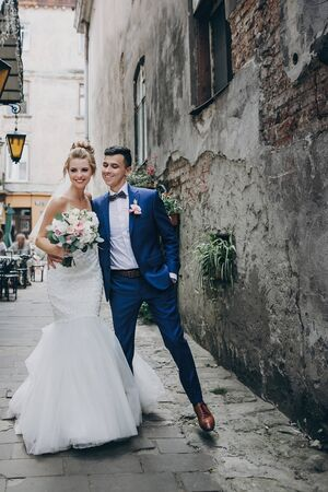 Stylish happy bride and groom walking in old city street. Gorgeous wedding couple of newlyweds embracing and smiling outdoors. Romantic moment