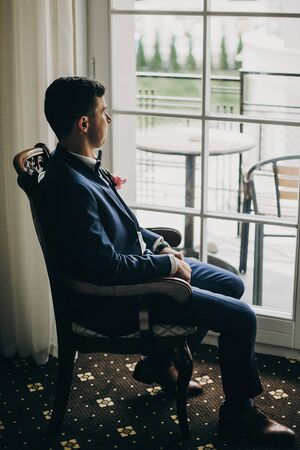 Stylish groom in blue suit, with bow tie and boutonniere with pink rose sitting in chair near window in hotel room. Morning preparation before wedding ceremony
