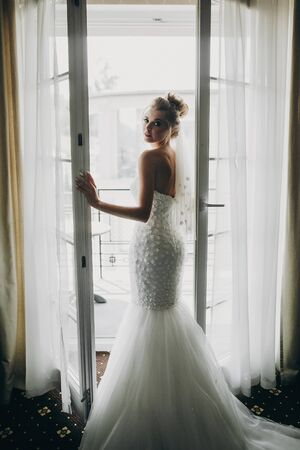 Stylish bride opening window balcony in soft light in hotel room. Back of gorgeous sensual bride in white gown. Morning preparation before wedding ceremony