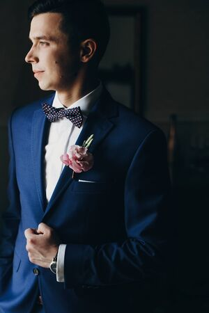 Stylish groom in blue suit, with bow tie and boutonniere with pink rose posing near window in hotel room. Morning preparation before wedding ceremony