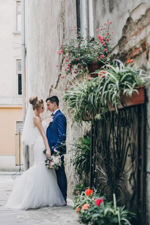 Stylish happy bride and groom posing in old european city street. Gorgeous wedding couple of newlyweds embracing  outdoors. Romantic moment