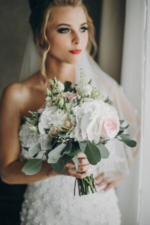 Stylish bride holding modern wedding bouquet and posing in soft light near window in hotel room. Gorgeous sensual bride portrait. Morning preparation before wedding ceremony