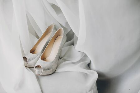 Stylish white shoes for bride on white tulle in soft morning light in hotel room. Morning preparation before wedding ceremony. Footwear for luxury event