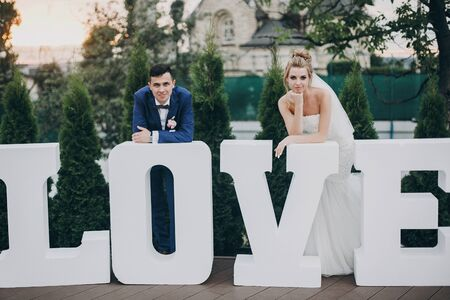 Stylish happy bride and groom posing at big love word in evening light at wedding reception outdoors. Gorgeous wedding couple of newlyweds having fun in evening park Фото со стока - 128326798