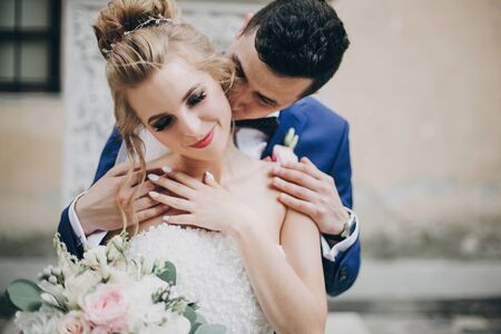 Stylish bride and groom kissing sensually in sunny european city street. Gorgeous wedding couple of newlyweds embracing at old buildings. Romantic moment 스톡 콘텐츠