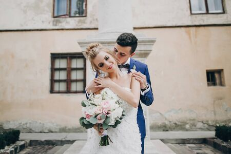 Stylish bride and groom kissing sensually in sunny european city street. Gorgeous wedding couple of newlyweds embracing at old buildings. Romantic moment Zdjęcie Seryjne - 128326804