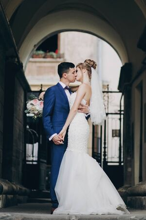 Stylish bride and groom gently kissing in sunny european city street. Gorgeous wedding couple of newlyweds embracing in old buildings. Romantic moment Stockfoto