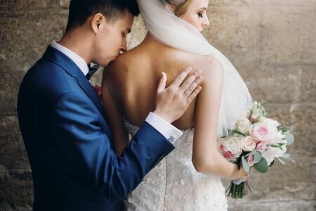 Stylish groom gently kissing beautiful bride with bouquet in shoulder, in city street, back view. Gorgeous wedding couple of newlyweds embracing at old buildings. Romantic moment 스톡 콘텐츠