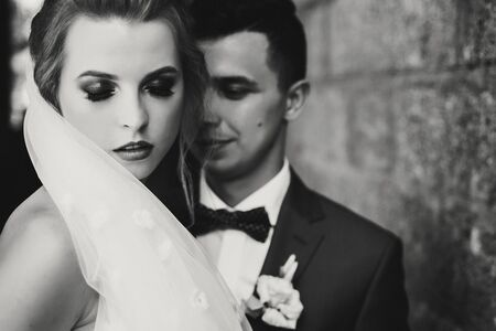 Stylish bride and groom gently embracing in european city street, face closeup. Gorgeous wedding couple of newlyweds sensually hugging at old buildings. Romantic moment