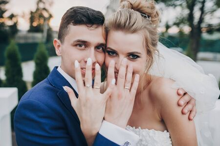Just married. Stylish happy bride and groom showing hands with wedding rings at wedding reception outdoors. Gorgeous wedding couple of newlyweds having fun