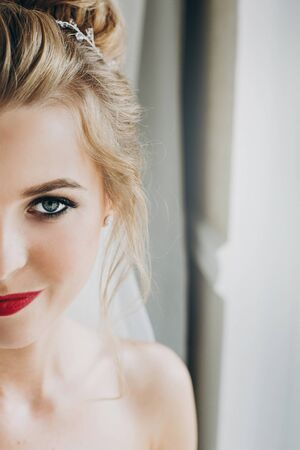 Stylish bride with amazing makeup posing in soft light near window in hotel room. Gorgeous sensual bride portrait with sexy look. Morning preparation before wedding ceremony 스톡 콘텐츠