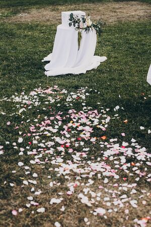 stylish floral decor of wedding aisle, rose petals on grass and modern wooden box for gifts from guests for wedding couple. Gift box on table with floral arrangement