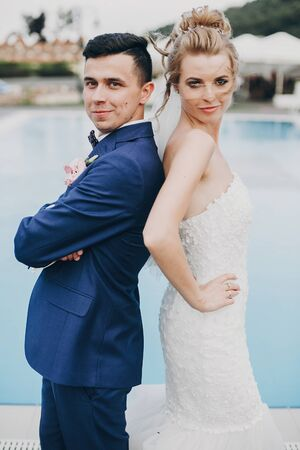 Stylish happy bride and groom posing at pool blue water at wedding reception in restaurant. Gorgeous wedding couple of newlyweds having fun after wedding ceremony outdoors 스톡 콘텐츠