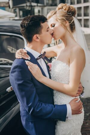 Stylish happy bride and groom kissing at old black retro car. Gorgeous wedding couple of newlyweds embracing after wedding ceremony. Romantic moment
