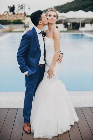 Stylish happy bride and groom kissing at pool blue water at wedding reception in restaurant. Gorgeous wedding couple of newlyweds embracing after wedding ceremony outdoors 스톡 콘텐츠