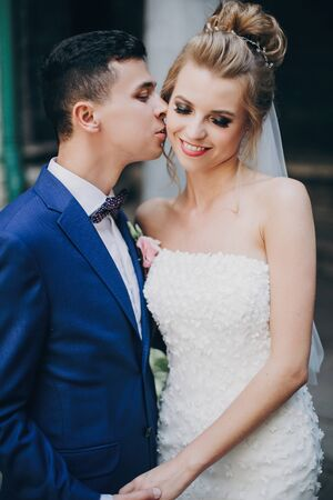Stylish bride and groom gently hugging in sunny european city street. Gorgeous wedding couple of newlyweds embracing in old buildings. Romantic moment 스톡 콘텐츠