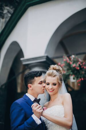 Stylish happy bride and groom smiling in sunny european city street. Gorgeous wedding couple of newlyweds embracing in old buildings. Romantic moment 스톡 콘텐츠
