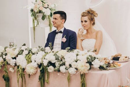Stylish bride and groom sitting together at beautiful pink centerpiece decorated with flowers at wedding reception in restaurant. Modern catering