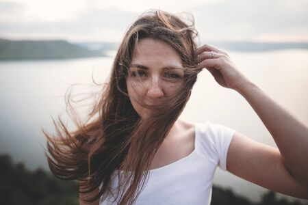 Traveler girl with windy hair relaxing on top of rock mountain, enjoying beautiful sunset view on river. Atmospheric moment. Copy space. Calm portrait of brunette woman in white shirt