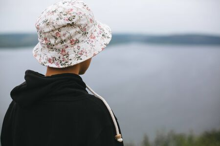 Hipster teenager in bucket hat standing on top of rock mountain and looking on river, view from back. Atmospheric calm moment. Wanderlust and travel. Copy space