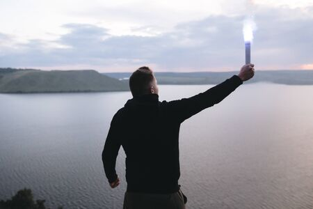 Protest concept. Brutal man holding blue flare torch in hand, standing on top of hill in evening with view on river.  Ultras hooligan with fire signal bomb. Atmospheric moment
