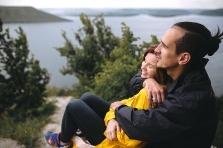 Happy hipster couple in raincoats sitting on top of rock mountain with beautiful view on river. Tourist couple hugging and sitting on windy cliff. Travel and wanderlust. Copy space