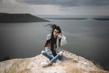 Stylish hipster girl with windy hair sitting on top of rock mountain with beautiful view on river. Young tourist woman relaxing on cliff. Travel and wanderlust. Copy space