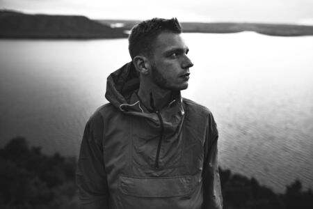 Portrait of hipster traveler in windbreaker on top of rock mountain with amazing view on river. Stylish guy exploring and traveling. Atmospheric moment. Copy space