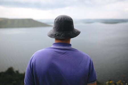 Hipster traveler in purple shirt  and bucket hat standing on top of rock mountain with amazing view on river. Young brutal guy exploring and traveling, back view. Copy space