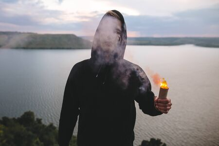 Stylish hipster guy holding smoke bomb with burning fire in hand, standing on top of rock mountain with amazing sunset view on river . Atmospheric moment. Copy space. Travel and explore